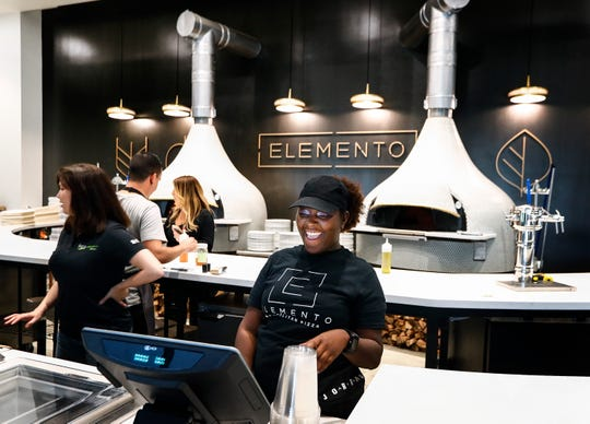 Elemento Neapolitan Pizza cashier Karesha Mans takes customers orders during a soft-opening for the new Crosstown Concourse pizzeria. The restaurant will adhere to the Neapolitan standard, which calls for certain types of tomatoes and cheeses, as well as flour for the dough. Cooking times and temperature are also fundamental to making authentic Neapolitan style pizza.