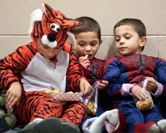 Giovanni Colon, left, and his twin brothers,  Jeremiah and Nehemiah enjoy some treats at a past Halloween party at Pabst Farms YMCA. The YMCA is hosting another celebration of Halloween Friday, Oct. 26.