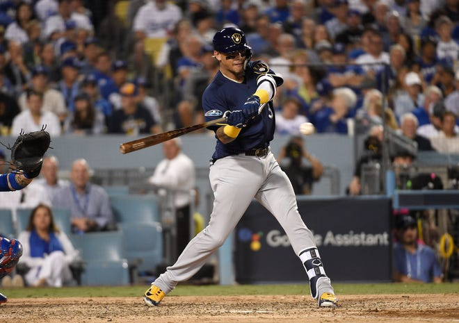 The Brewers' Orlando Arcia hits a two-run home run over the right field wall during the seventh inning of Game 3 on Monday.