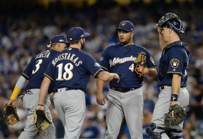 Catcher Erik Kratz and members of the Brewers infield congregate on the mound to congratulate starter Jhoulys Chacin as manager Craig Counsell is on his way out to make a pitching change in the sixth inning of Game 3 on Monday. Chacin gave the Brewers a sharp start with 5 1/3 shutout innings of three-hit ball with two walks and six strikeouts.
