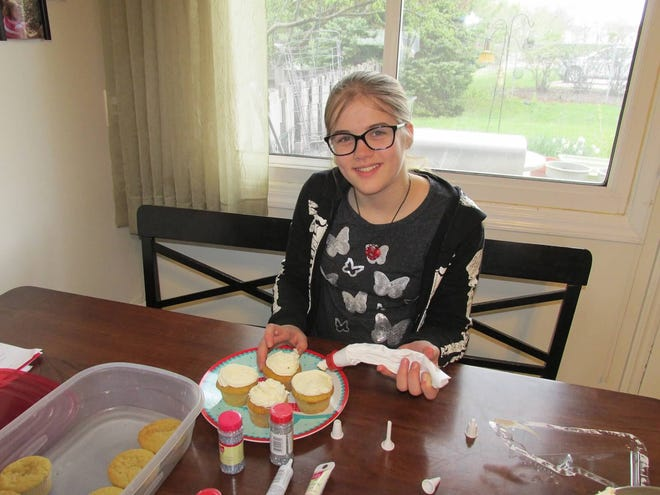"Morgan Geyser decorates cupcakes on her 12th birthday two weeks prior to her arrest. Geyser, now 16, has been sentenced to 40 years in a mental health institution after nearly stabbing a classmate to death in May 2014. The zip-up jacket she is wearing in this photo is similar to the outfit worn by the actress who plays her in the Lifetime movie, ""Terror in the Woods."""