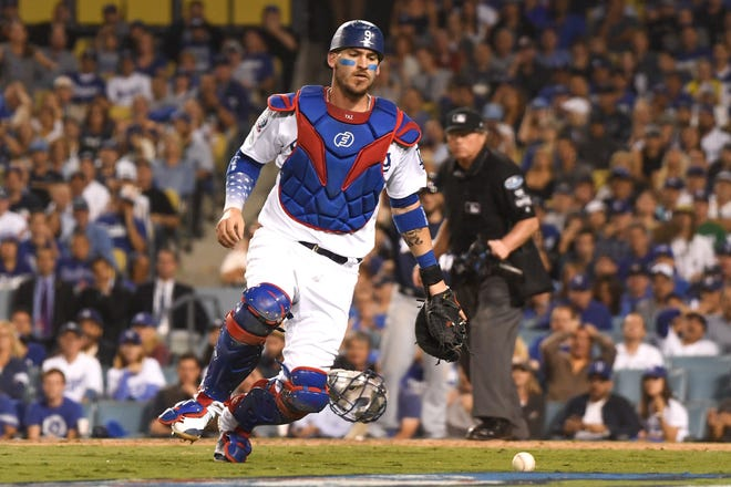 Dodgers catcher Yasmani Grandal is unable to track down a wild pitch in time as Travis Shaw (not pictured) of the Brewers is able to score from third during the sixth inning of Game 3 on Monday.