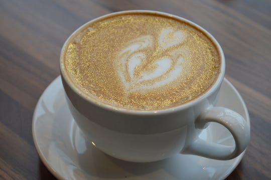 A glitter gold latte is a vanilla latte that is topped with edible glitter before the milk is added.