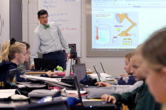 Instructor has students adjust one variable in a photosynthesis simulation, then track the amount of oxygen produced during a sixth grade science class at Kettle Moraine Middle School on Oct. 15.