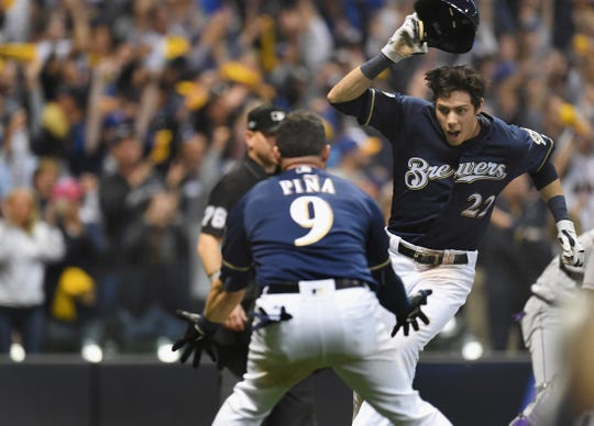 Christian Yelich of the Milwaukee Brewers celebrates with Manny Pina as he runs home to score the winning run in Game 1 of the NLDS.