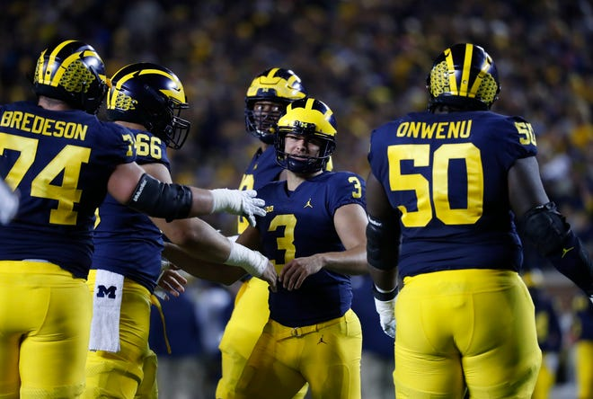 Michigan players congratulate kicker Quinn Nordin on his field goal that gave the Wolverines a 24-7 lead over Wisconsin on Saturday night in Ann Arbor.