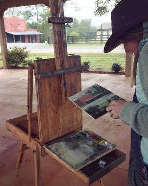 Artist Laura Vahlberg of Montgomery braved wind and rain to paint under the Veterans Pavilion during the 2017 Paint Out.
