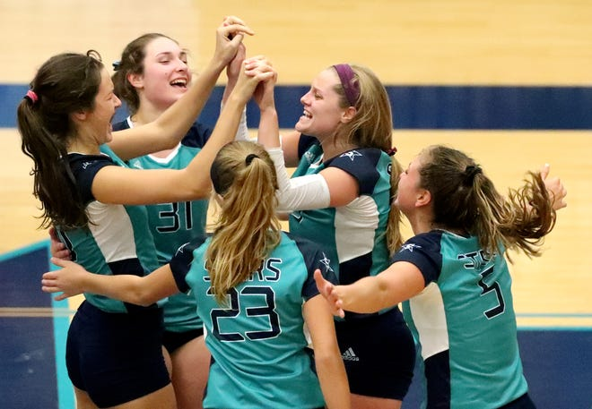 Siegel players celebrate a point during Tuesday's Class AAA state volleyball tournament at Siegel High.