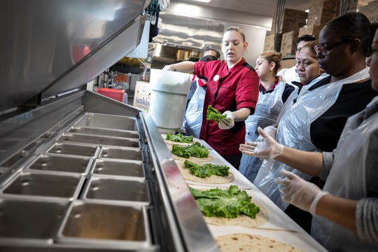 Sara Harris, a certified trainer for Chick-fil-A, teaches employees how to make a wrap at Chick-fil-A's new Midtown location during an open house Oct. 16, 2018.