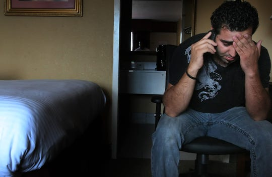 Family member Farzin Abdi, nephew of Sahel Kazemi talks to his mother in his hotel room. Abdi flew in from Florida to tke home Kazemi's body.  (July 5 , 2009 JOHN PARTIPILO/THE TENNESSEAN)