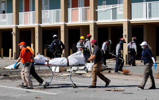 In this photo taken Oct. 12, 2018, a body being removed after being discovered during the search of a housing structure in the aftermath of Hurricane Michael in Mexico Beach, Fla.