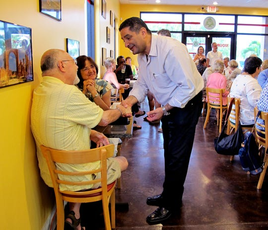 Moura Bistro owner Nabil Bassil, center, greets guests in June 2016 at his Lebanese restaurant in Meridian Marketplace in North Naples.