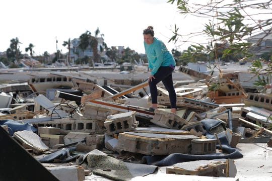 In this Oct. 11, 2018 file photo, Mishelle McPherson looks for her friend Agnes Vicari in the rubble of her home in Mexico Beach, Fla.