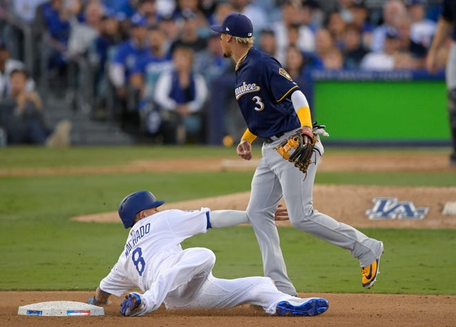Los Angeles Dodgers' Manny Machado is called for interference after holding Milwaukee Brewers' Orlando Arcia on a double play attempt during the fourth inning of Game 3 of the National League Championship Series baseball game Monday, Oct. 15, 2018, in Los Angeles. (AP Photo/Mark J. Terrill)