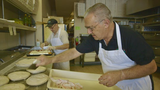 Owner Charlie Osso lays out dough for pizza at Rudy's.