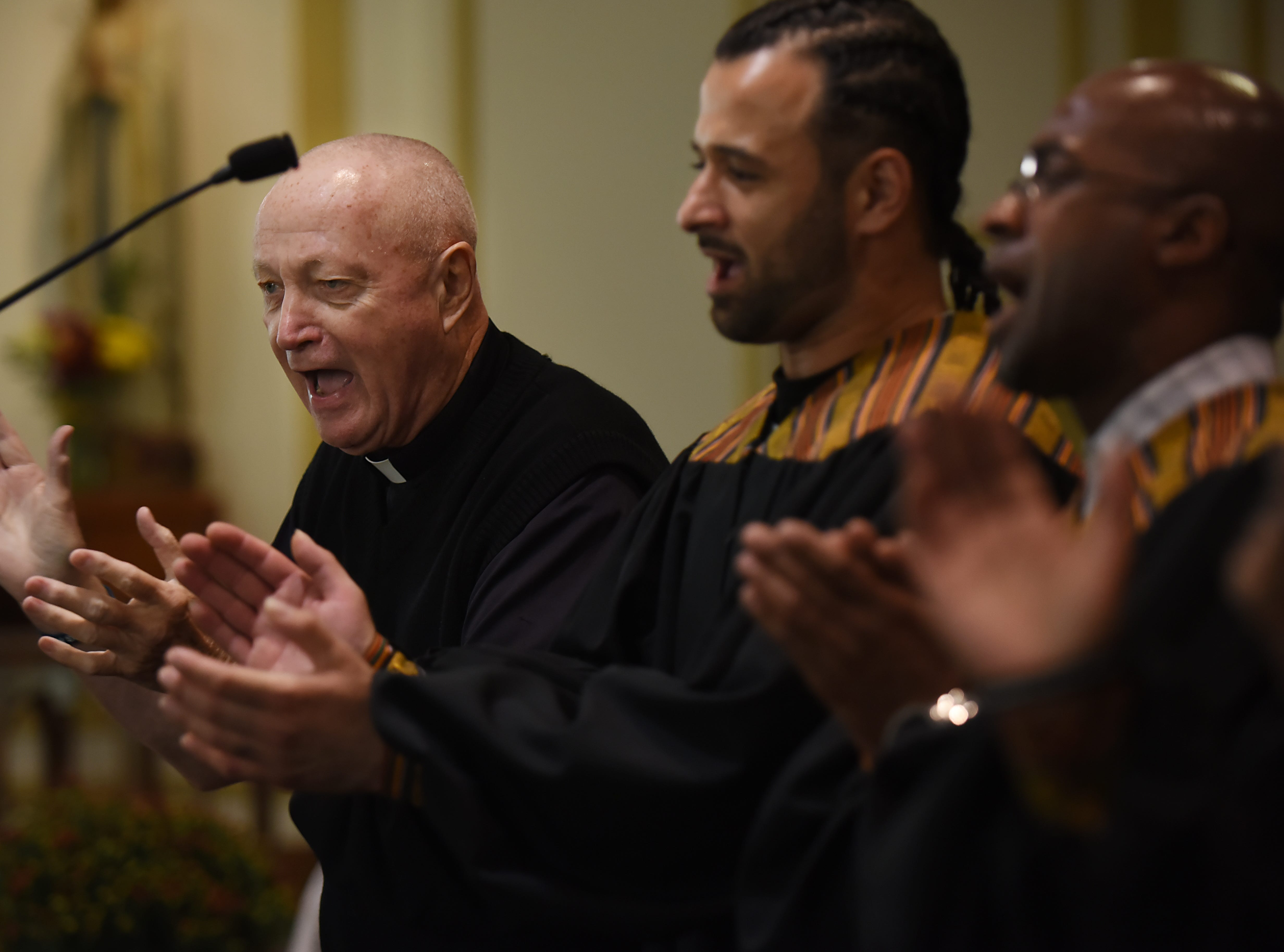 Father Bill Naughton sings with members of the Straight & Narrow Gospel Choir at St. Joseph's Roman Catholic Church in Lincoln Park.