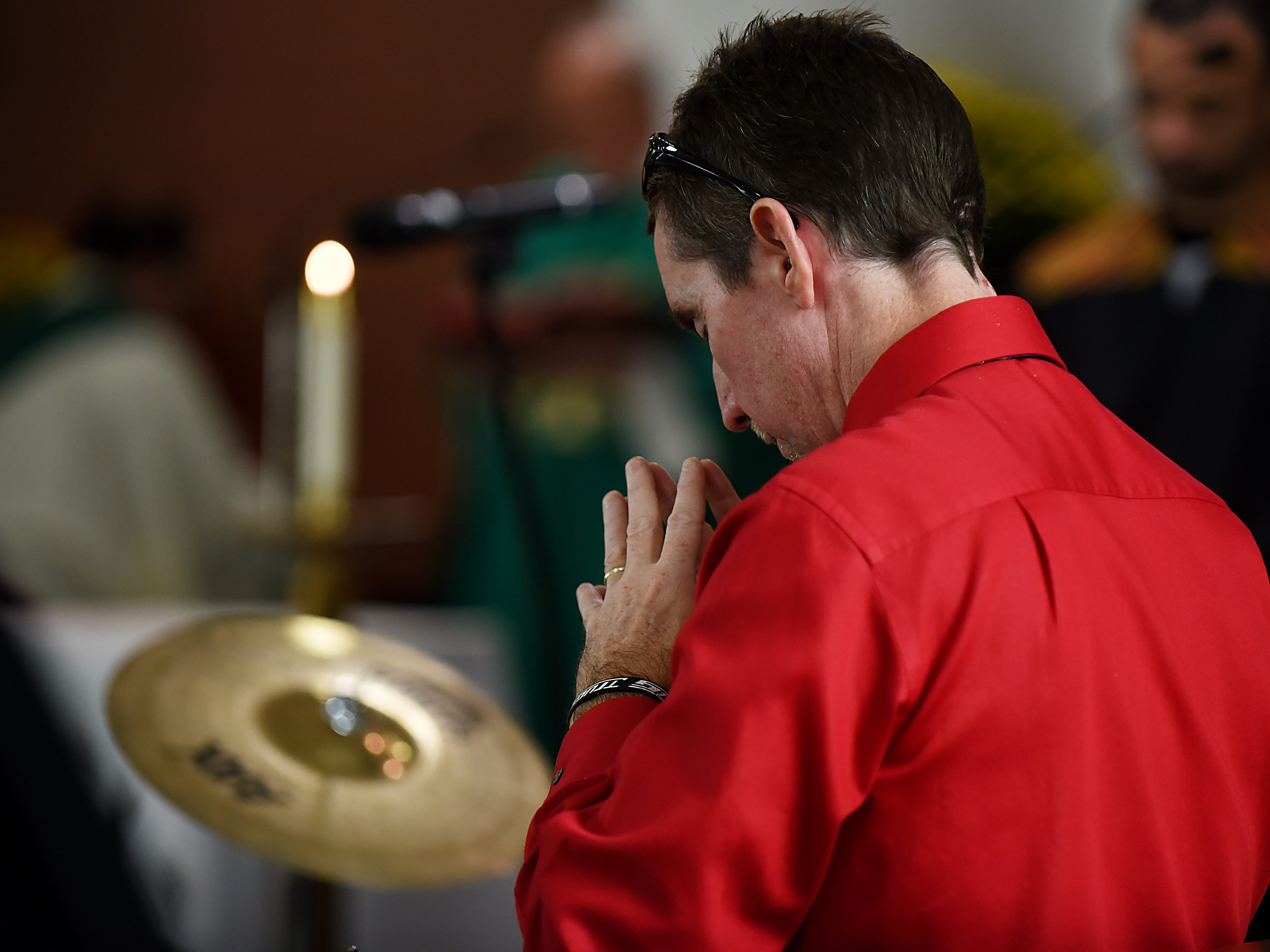 John, the drummer for the Straight and Narrow Choir, pauses to pray during a performance at Saint Joseph's Roman Catholic Church in Lincoln Park on Sunday October 14, 2018.
