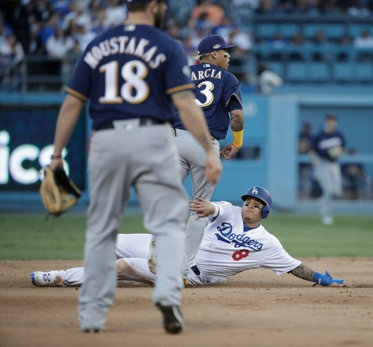 Los Angeles Dodgers' Manny Machado is called for interference after holding Milwaukee Brewers' Orlando Arcia on a double play attempt during the fourth inning of Game 3 of the National League Championship Series baseball game Monday, Oct. 15, 2018, in Los Angeles. (AP Photo/Jae Hong)