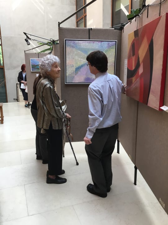 Andrew Weatherly speaks to a attendee about his art.
