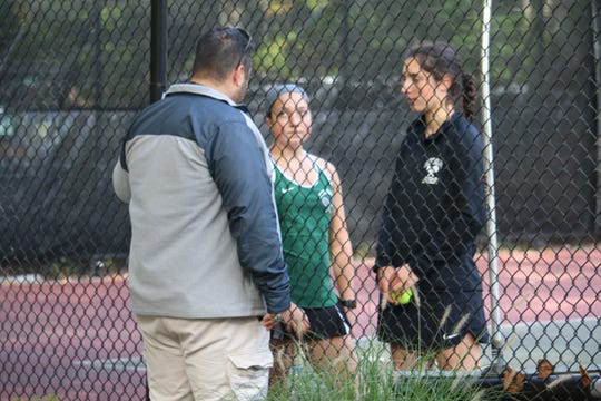 Kinnelon second doubles players Nicole VanNiekerk, left, and Victoria Kaufman consult with coach Jon Cataldi during Tuesday's state sectional final in Kinnelon.