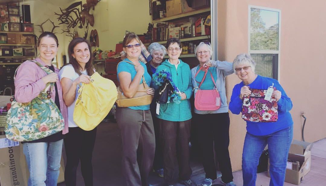 P.E.O. members preparing for a previous purse auction.  Left to right are Anna Dye, Amanda Pryor, Pam Weber, Marie Martin, Karen Murphy, Nancy Champlin, Sue Teller-Marshall.