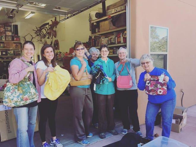 P.E.O. members preparing for a previous purse auction. Left to right are Anna Dye, Amanda Pryor, Pam Weber, Marie Martin, Karen Murphy, Nancy Champlin, Sue Teller-Marshall.
