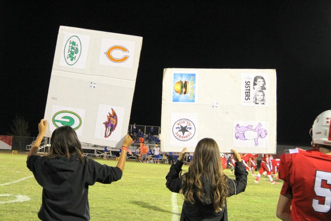 Loving's managers hold up signs for the Falcon defense. Each picture, along with its orientation on the card, represents a different play, defensive look or plain gibberish to confuse the opposition.