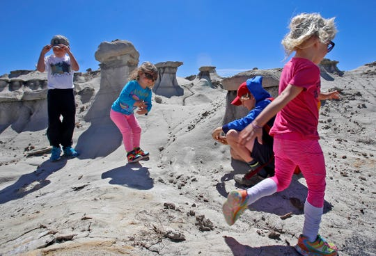 Jackson Fetz, left, Lyra Boggs, Cy Wilsey and Emma Wilsey take a walk April 23, 2016, during a Families on Foot Hike at the Bisti/De-Na-Zin Wilderness Area presented by the Farmington Museum at Gateway Park.