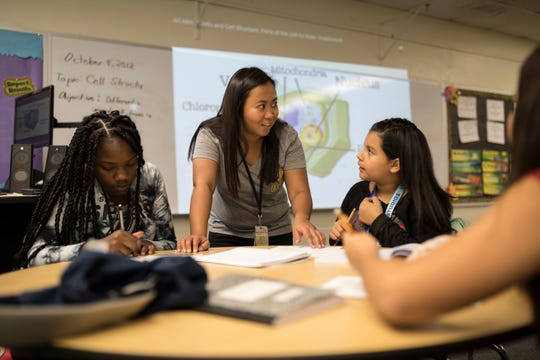 Filipino teacher Cindy Serrano assists Nevaeh Baker, left, and Kamilah Cedillo with an in-class exercise during her biology class at Heizer Middle School. Serrano taught for five years in the Philippines and is in her second year of instruction in Hobbs, NM.