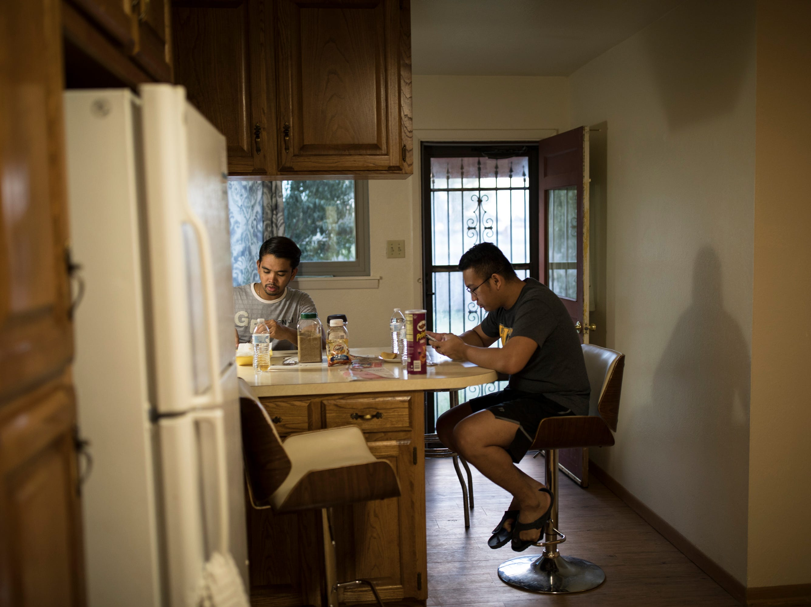 Ronell Mangilit, left, and Kim Alrod Araza hang out in the kitchen of the home they share with two other teachers in Hobbs, NM. Strapped with payments towards their debt to recruiters, many of the teachers still feel the risk is worth their while. Starting teacher salaries in New Mexico are amongst the lowest in the nation at $36,180 whereas the teachers are accustomed to $400-$800 per month in their home country.