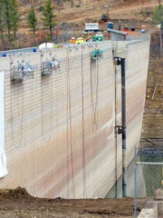 Teams worked on the exterior of the Grindstone  Dam in preparation for installation of the liner.