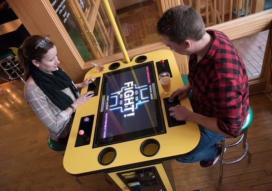 Sinead and Jason James of Farmington Hills play a video game at 1 Up Arcade Bar in downtown Farmington.