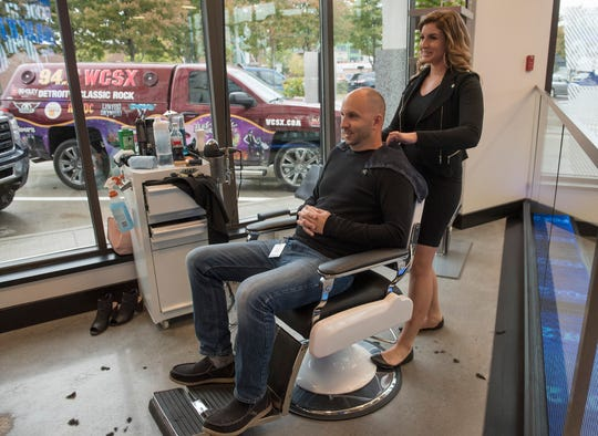 Dave Schnoblen, from Macomb Twp, gets a haircut from stylist Melissa Martin. The WCSX machine is parked outside. With glass walls, the studio is visible to customers.