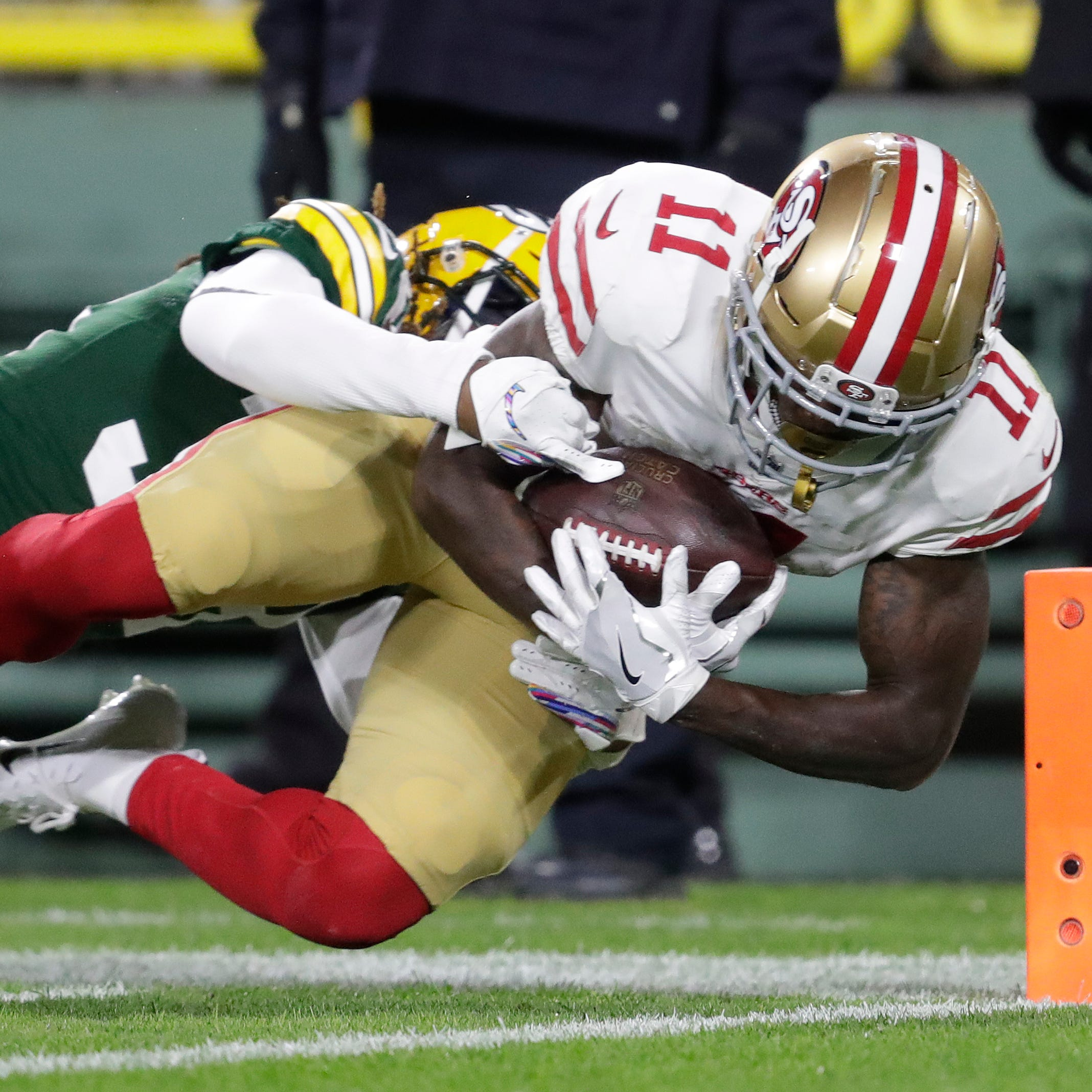 San Francisco 49ers wide receiver Marquise Goodwin (11) dives into the end zone for a touchdown against Green Bay Packers cornerback Tramon Williams (38) in the second quarter during their football game Monday, Oct. 15, 2018, at Lambeau Field in Green Bay, Wis. 