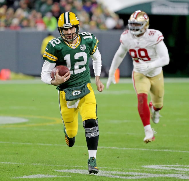 Green Bay Packers quarterback Aaron Rodgers (12) scrambles for a first down on a fourth down play against the San Francisco 49ers at Lambeau Field Monday, October 15, 2018 in Green Bay, Wis.