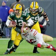Green Bay Packers quarterback Aaron Rodgers (12) gets sacked by defensive tackle Sheldon Day (96) against the San Francisco 49ers at Lambeau Field Monday, October 15, 2018 in Green Bay, Wis.