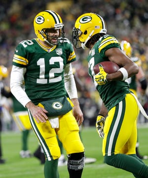 Green Bay Packers quarterback Aaron Rodgers (12) celebrates a touchdown connection with Davante Adams (17) late in the first quarter during their football game Monday, Oct. 15, 2018, at Lambeau Field in Green Bay, Wis.