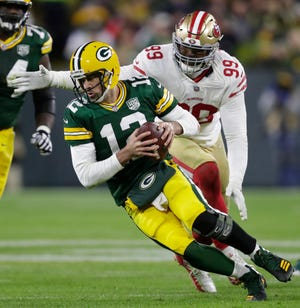 Green Bay Packers quarterback Aaron Rodgers (12) is sacked by San Francisco 49ers defensive tackle DeForest Buckner (99) in the third quarter during their football game Monday, Oct. 15, 2018, at Lambeau Field in Green Bay, Wis.