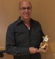 Ron Celona poses with his Desert Stars Award after winning for Outstanding Director of a Drama/Professional