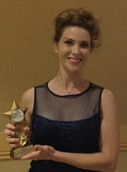 Se Layne poses with one of the three Desert Stars Awards she won Sunday for her work at Palm Canyon Theatre.