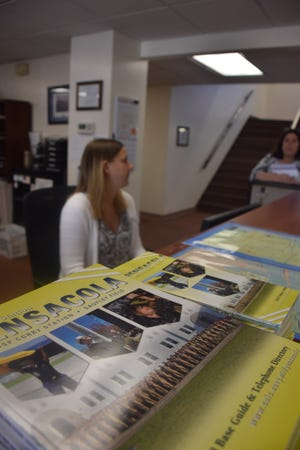 Ariel Raymond with Pensacola Naval Air Station's Fleet and Family Services Office prepares Tuesday to welcome sailors and their families from Panama City.