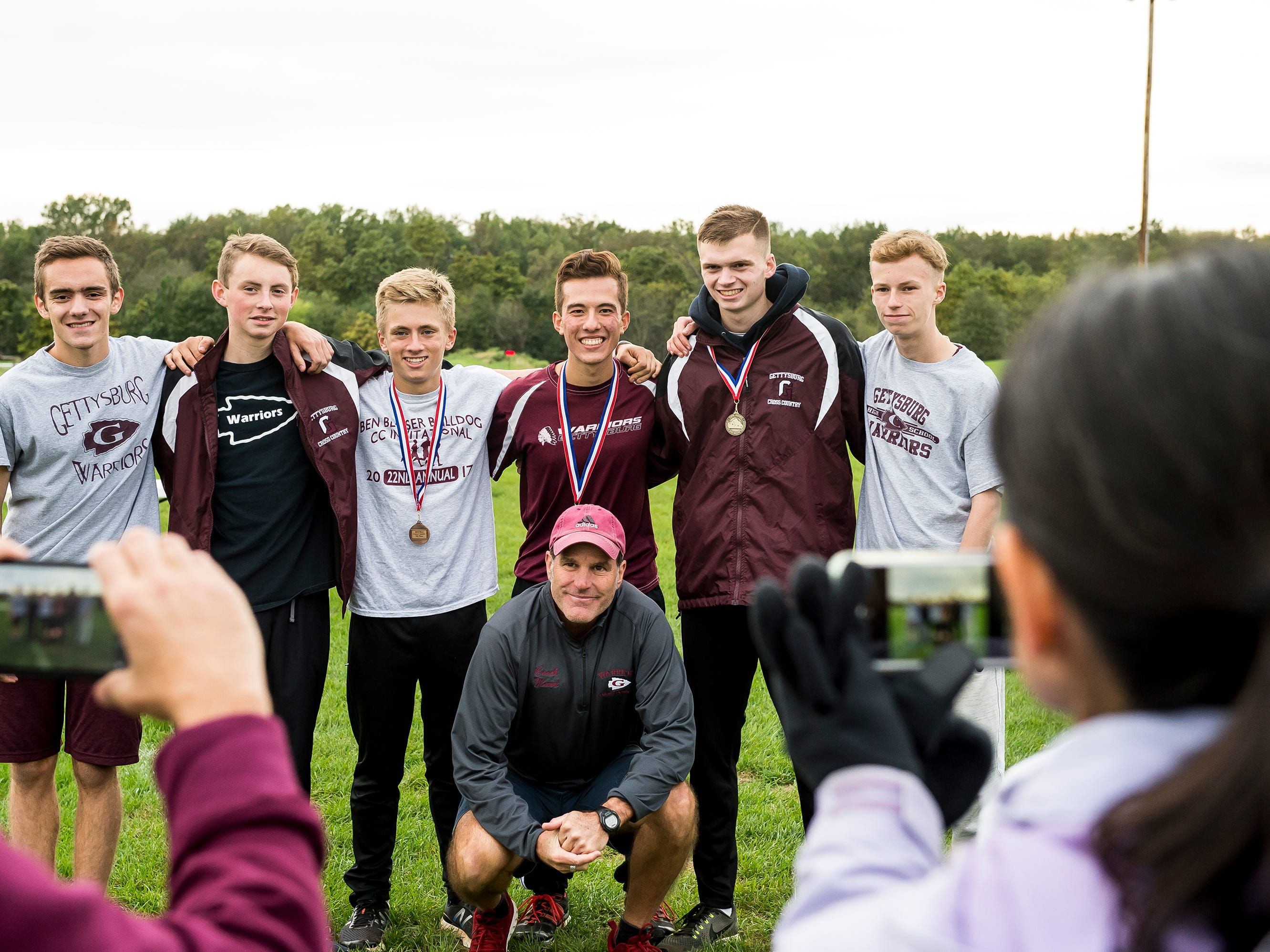Gettysburg boys' cross country runners pose for photos with coach Brian Mount following the YAIAA cross country championships at Gettysburg Area High School on Tuesday, October 16, 2018. The Warriors finished second in the team rankings.