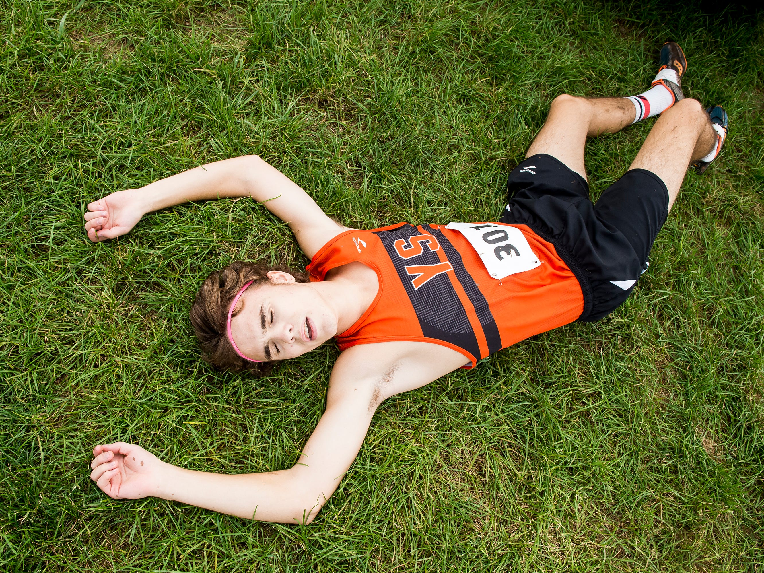 York Suburban's Jarrett Raudensky rests in the grass after competing in the YAIAA cross country championships at Gettysburg Area High School on Tuesday, October 16, 2018. Raudensky finished third in the boys' race with a time of 16:48.9