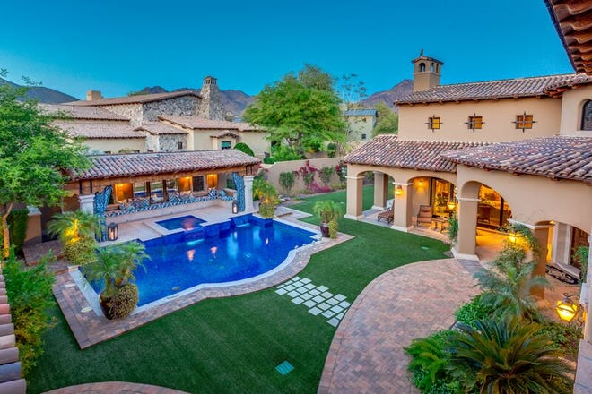 The mansion purchased by Jerry R. Smith has a Venetian tiled pool, a courtyard garden, and a pool side cabana.
