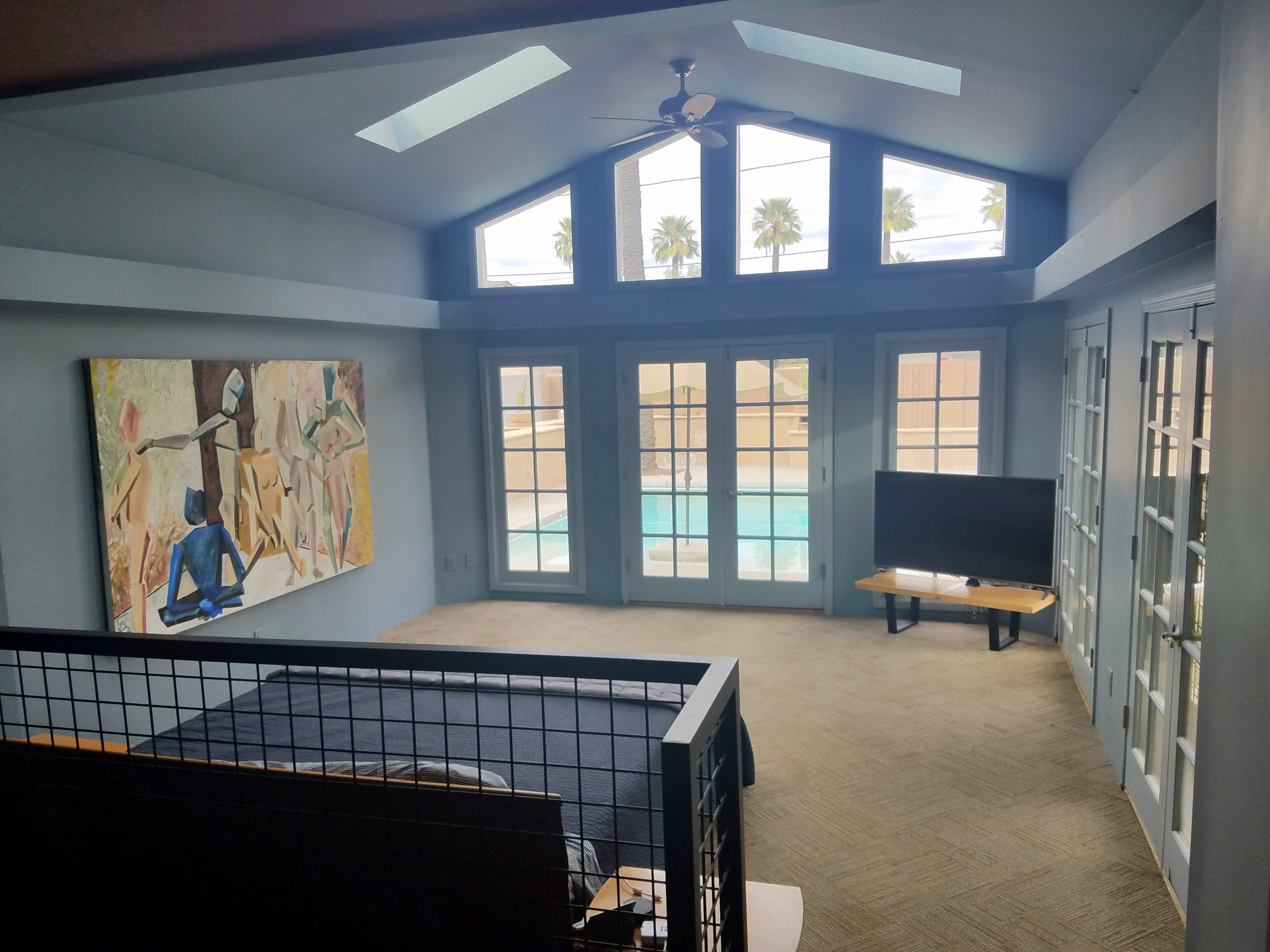The master bedroom, tucked beyond the master bath, is actually recessed from an elevated, open closet space, and looks out to the home's backyard pool area thanks to French doors on two walls.