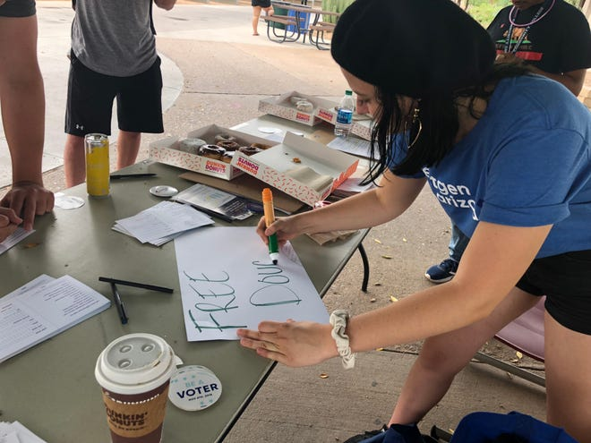 Bailey Price, a NextGen fellow in Arizona, writes a sign for free donuts at a voter registration tabling at Mesa Community College on Sept. 19.
