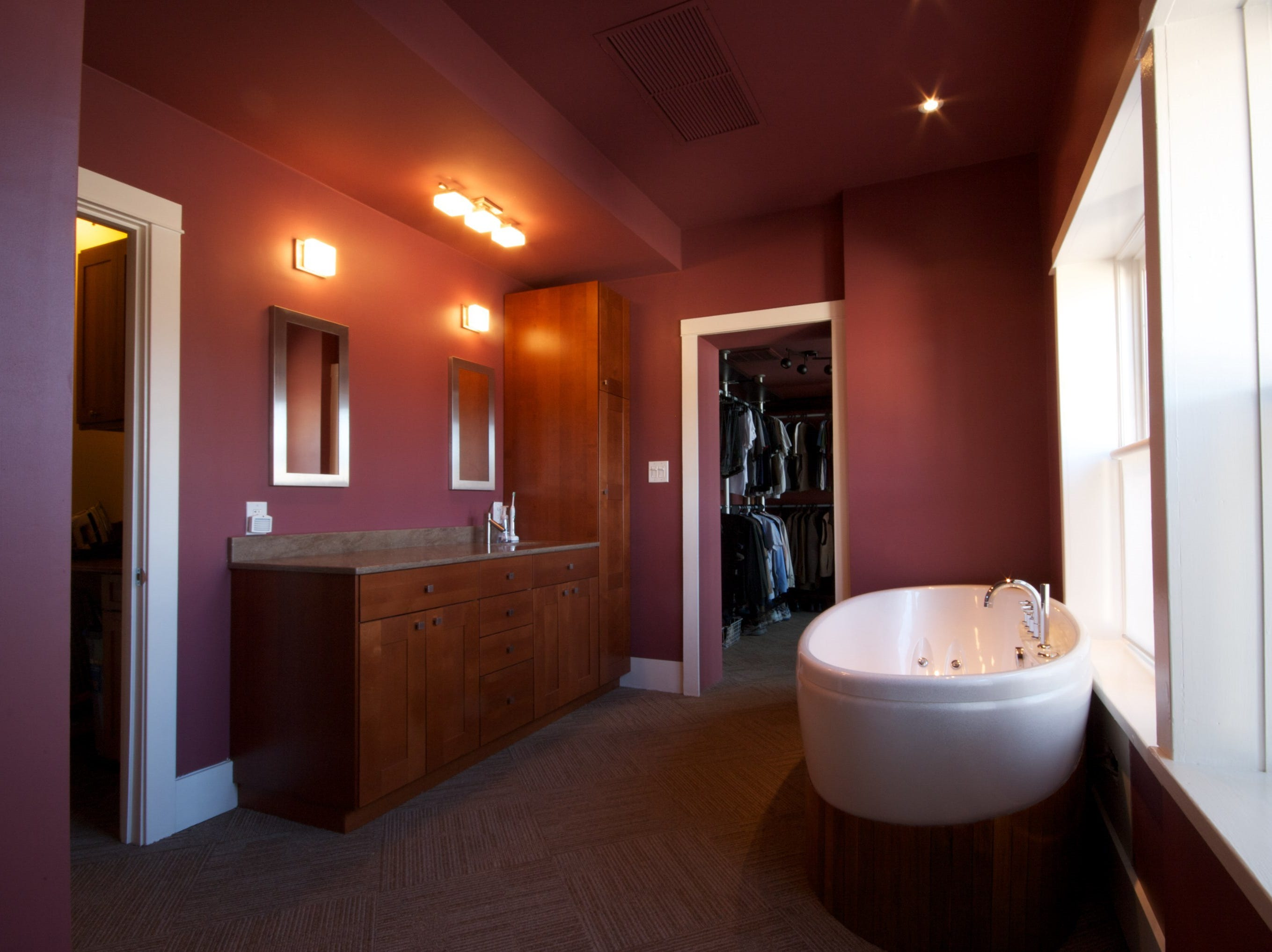 The entry to the master suite is actually through the master bathroom, which features a standalone, jetted tub.