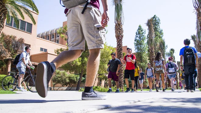 Arizona State University students take Palm Walk between classes on  the Tempe campus on Sept. 11, 2017.