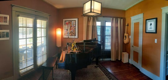 Adjacent to the home's front room is a music room, which includes a baby grand piano and an acoustic guitar.