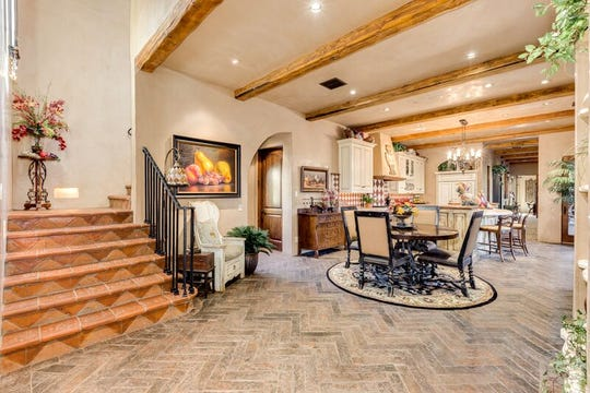 The two-story Tuscan estate has architectural design features including double barrel vaulted ceilings and custom herringbone patterned tile work.